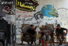 Members of the Iraqi police forces sit outside a building in the city of Fallujah on June 30, 2016 after they've recaptured the city from Islamic State (IS) group jihadists. Ahmad al-Rubaye/AFP
