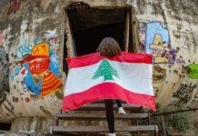Une fille arborant le drapeau libanais à l'entrée de l'Oeuf, structure en béton du Centre ville de Beyrouth. Photographie circulant sur les réseaux sociaux. Crédit Photo: DR (droit réservé)